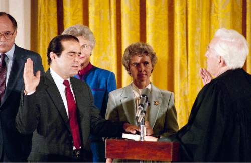 FILE - In this Friday, Sept. 26, 1986 file photo, retiring Chief Justice Warren Burger, right, administers an oath to Associate Justice Antonin Scalia, as Scalia's wife, Maureen, holds the bible during ceremonies in the East Room of White House, Washington. Scalia was the 103rd person to sit on the court. On Saturday, Feb. 13, 2016, the U.S. Marshals Service confirmed that Scalia has died at the age of 79. (AP Photo/Charles Tasnadi)