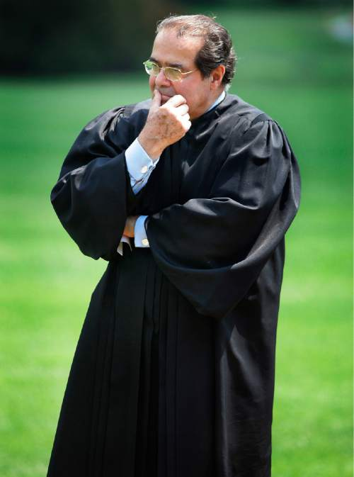 FILE - In this June 7, 2006 file photo, Supreme Court Justice Antonin Scalia listens to President Bush speak during a swearing-in ceremony on the South Lawn at the White House in Washington. On Saturday, Feb. 13, 2016, the U.S. Marshall's Service confirmed that Scalia has died at the age of 79. (AP Photo/Ron Edmonds, File)