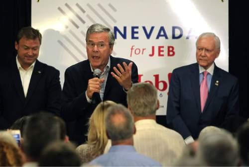 Nevada Republican Sen.  Dean Heller, left, and Utah Republican Sen. Orrin Hatch, right, listen to Republican presidential candidate Jeb Bush, center, speak after endorsing Bush, during a campaign stop, Wednesday, Aug. 12, 2015, in Reno Nev. (AP Photo/Lance Iversen)