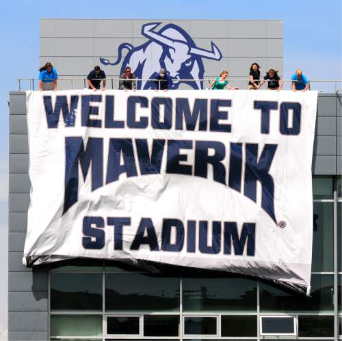 John Zsiray  |  Herald Journal  A group of people unfurl a banner announcing the name change of Romney Stadium to Maverik Stadium from the roof of the Jim and Carol Laub Athletics-Academics Complex during the Utah State spring football game on Saturday April 11, 2015.