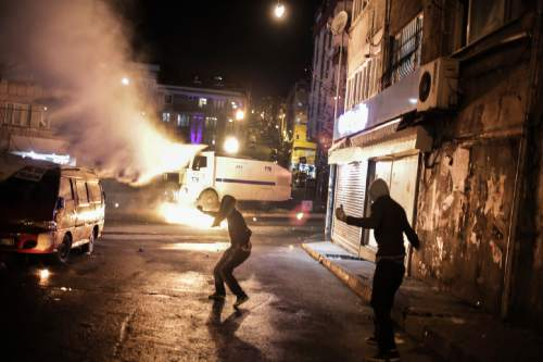 Protesters run after they threw a petrol bomb against a Turkish police water cannon during clashes in Istanbul, Sunday, Feb. 14, 2016, between police forces and people protesting against security operations against Kurdish rebels in southeastern Turkey. Turkey imposed curfews in mainly Kurdish towns and districts in December while its security forces battled militants linked to the Kurdistan Workers' Party, or PKK, who set up barricades, dug trenches and primed explosives in the areas they have declared to be under Kurdish self-rule. (AP Photo/Cagdas Erdogan)