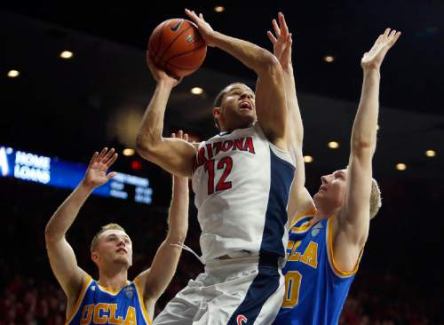 Arizona forward Ryan Anderson (12) shoots between UCLA's Bryce Alford, left, and Thomas Welsh during the second half of an NCAA college basketball game, Friday, Feb 12, 2016, in Tucson, Ariz. Arizona defeated UCLA 81-75. (AP Photo/Rick Scuteri)