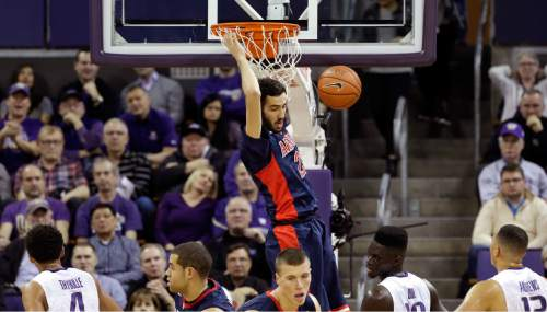 Arizona's Mark Tollefsen, top, dunks against Washington during the first half of an NCAA college basketball game Saturday, Feb. 6, 2016, in Seattle. (AP Photo/Elaine Thompson)