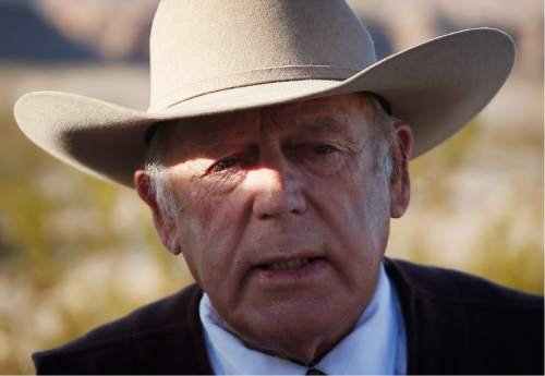 FILE - In this Jan. 27, 2016, file photo, rancher Cliven Bundy stands along the road near his ranch in Bunkerville, Nev. Bundy, the father of the jailed leader of the Oregon refuge occupation, and who was the center of a standoff with federal officials in Nevada in 2014, was arrested in Portland on Wednesday, Feb. 10,, the FBI said Thursday, Feb. 11, 2016. (AP Photo/John Locher, File)