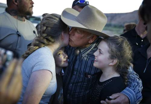 Rancher Cliven Bundy kisses supporter Claudia Riffenburg during an event Saturday, April 11, 2015, in Bunkerville, Nev. Bundy was holding the event to celebrate the one year anniversary since the Bureau of Land Management's failed attempt to collect his cattle.(AP Photo/John Locher)