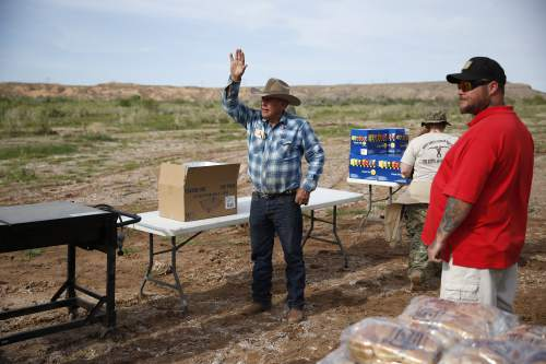 Rancher Cliven Bundy waves to a supporter  during an event Friday, April 10, 2015, in Bunkerville, Nev. Bundy is holding the event to celebrate the one year anniversary since the Bureau of Land Management's failed attempt to collect his cattle. (AP Photo/John Locher)