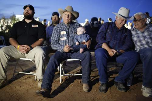 Rancher Cliven Bundy holds his five-month-old grandson Roper Cox at an event Saturday, April 11, 2015, in Bunkerville, Nev. Bundy is holding the event to celebrate the one year anniversary since the Bureau of Land Management's failed attempt to collect his cattle.(AP Photo/John Locher)