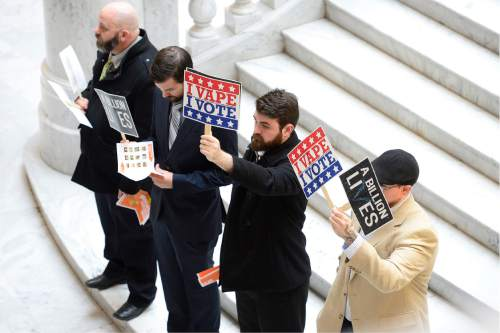 "Scott Sommerdorf   |  The Salt Lake Tribune Pro e-cigarette supporters holds signs near the large ""OUTRAGE!"" group who were there to push for a bill that would change the allowed age to buy tobacco products from 19 to 21 during a rally in the Capitol rotunda, Wednesday, February 17, 2016."