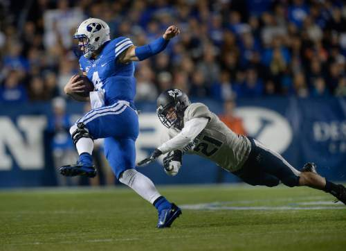 Scott Sommerdorf  |  Tribune file photo BYU QB Taysom Hill runs and eludes Utah State Aggies safety Brian Suite (21) during first half play. He later would run a similar play and be injured on a tackle by Suite. Utah State led BYU 28-14 at the half in Provo, Friday, October 1, 2014.