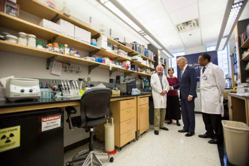 Vice President Joe Biden speaks with Nobel Laureate Dr. Paul Modrich, left, as Dr. A. Eugene Washington, Chancellor for Health Affairs at Duke University, right, and Vickers Burdett, wife of  Washington, middle listen in a laboratory at Duke University School of Medicine in Durham, N.C. Wednesday, Feb. 10, 2016. Biden visited Duke to speak about his Cancer Moonshot initiative. (AP Photo/Ben McKeown)