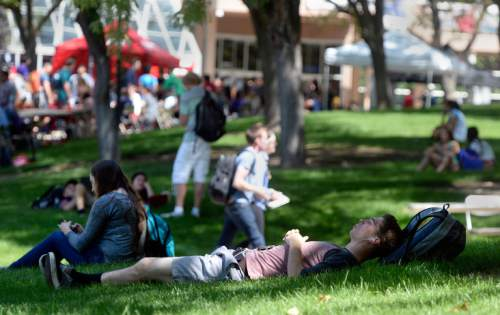 Al Hartmann     The Salt Lake Tribune Students at the University of Utah walk from classes and some hang out in the shade to beat the heat at the Olpin Union building for the first day of Fall 2015 classes.