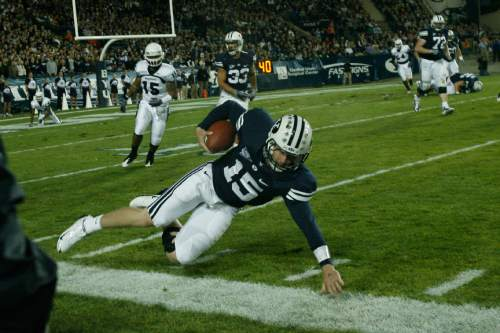 Photo by Chris Detrick  |  The Salt Lake Tribune  Brigham Young's Max Hall #15 dives for extra yards during the first half of the game at LaVell Edwards Stadium Friday October 2, 2009. BYU is winning the game 21-7.