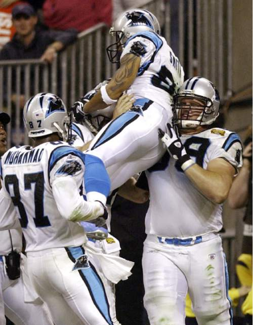 Carolina Panthers tackle Jordan Gross, right,  lifts wide receiver Steve Smith after Smith scored the team's first touchdown in the second quarter against the New England Patriots during Super Bowl XXXVIII in Houston, Sunday, Feb. 1, 2004. At left is the Panthers' Muhsin Muhammad (87). (AP Photo/Elise Amendola)