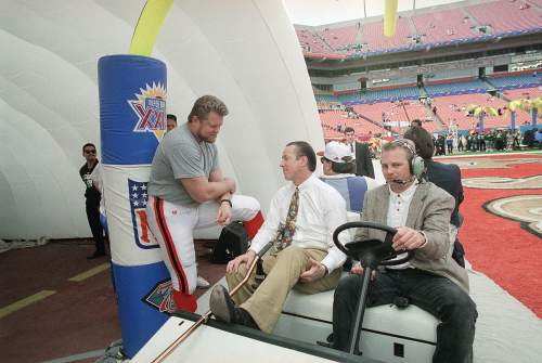 San Francisco 49ers center Bart Oates (66) talks with Buffalo Bills quarterback Jim Kelly, sitting in a golf cart carrying a crutch, in Miami's Joe Robbie Stadium on Sunday, Jan. 29, 1995, (AP Photo/Lenny Ingelzi)