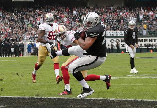 Oakland Raiders tackle Donald Penn (72) scores on a 3-yard touchdown pass from quarterback Derek Carr (4) in front of San Francisco 49ers safety Eric Reid (35) during the second quarter of an NFL football game in Oakland, Calif., Sunday, Dec. 7, 2014. (AP Photo/Marcio Jose Sanchez)