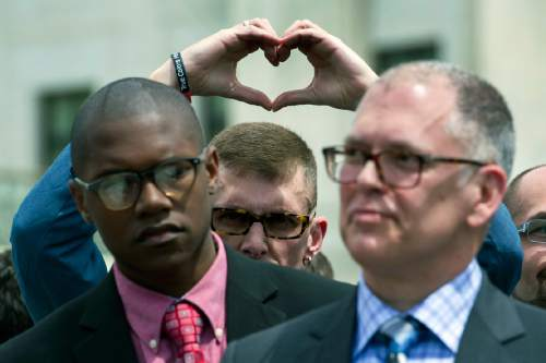 Plaintiff Rev. Maurice Blanchard, of Louisville, Ky., makes heart with his hands behind plaintiff plaintiff James Obergefell of Ohio, right, as they stand outside of the Supreme Court in Washington, Tuesday, April 28, 2015, following a hearing on same-sex marriages. (AP Photo/Cliff Owen)