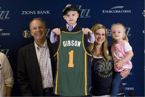 "SALT LAKE CITY, UT - OCTOBER 06:  (L-R) Utah Jazz President Randy Rigby President, JP Gibson #1 of the Utah Jazz and Megan Gibson JP's Mom and sister Elsie hold up his jersey after signing his one day-day contract with the Utah Jazz JP has Acute Lymphoblastic Leukemia and is part of the ""Anything Can Be"" project prior to the open scrimmage at EnergySolutions Arena on October 06, 2014 in Salt Lake City, Utah. NOTE TO USER: User expressly acknowledges and agrees that, by downloading and or using this Photograph, User is consenting to the terms and conditions of the Getty Images License Agreement. Mandatory Copyright Notice: Copyright 2014 NBAE (Photo by Melissa Majchrzak/NBAE via Getty Images)"
