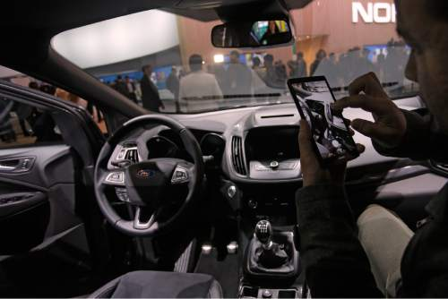 A man takes photographs with a phone inside the new Ford Kuga SUV car, which features its latest connectivity and driver-assisted technology, during the Mobile World Congress Wireless show, the world's largest mobile phone trade show, in Barcelona, Spain, Monday, Feb. 22, 2016. (AP Photo/Francisco Seco)