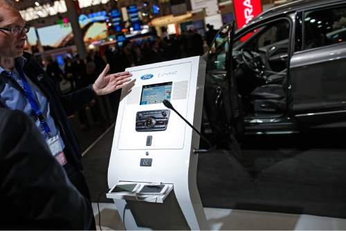 A Ford worker talks to a visitor about the new Ford Kuga SUV features in connectivity and driver-assisted technology during the Mobile World Congress Wireless show, the world's largest mobile phone trade show, in Barcelona, Spain, Monday, Feb. 22, 2016. (AP Photo/Francisco Seco)