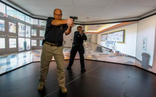 Trent Nelson  |  The Salt Lake Tribune Unified Police Deputy Chief Shane Hudson and Range Master Nick Roberts run through a school shooting simulation while demonstrating a new five-screen training simulator used to put officers through realistic situations in Salt Lake City, Thursday November 7, 2013.