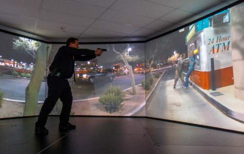 Trent Nelson  |  The Salt Lake Tribune Unified Police Range Master Nick Roberts confronts a man holding a knife to a woman's neck while demonstrating a new five-screen training simulator used to put officers through realistic situations in Salt Lake City, Thursday November 7, 2013.