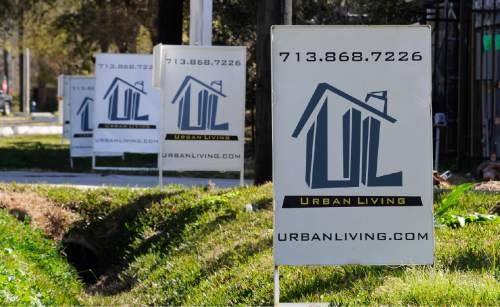 """In this Tuesday, Feb. 16, 2016, photo, """"For Sale"""" signs are stacked up outside a new complex of townhouses in Houston. On Tuesday, Feb. 23, 2016, the Standard & Poor's/Case-Shiller 20-city home price index is released. (AP Photo/Pat Sullivan)"""