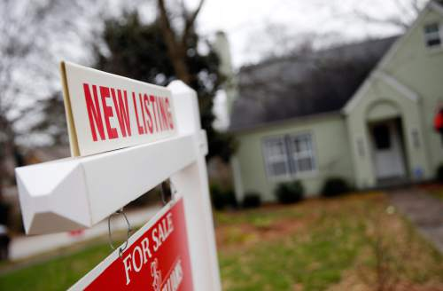 """In this Tuesday, Jan. 26, 2016, photo, a """"For Sale"""" sign hangs in front of an existing home in Atlanta. On Wednesday, Feb. 24, 2016, the Commerce Department reports U.S. home sales crept upward in January, a sign that demand for housing remains strong amid signs of slower growth across the broader economy. (AP Photo/John Bazemore)"""