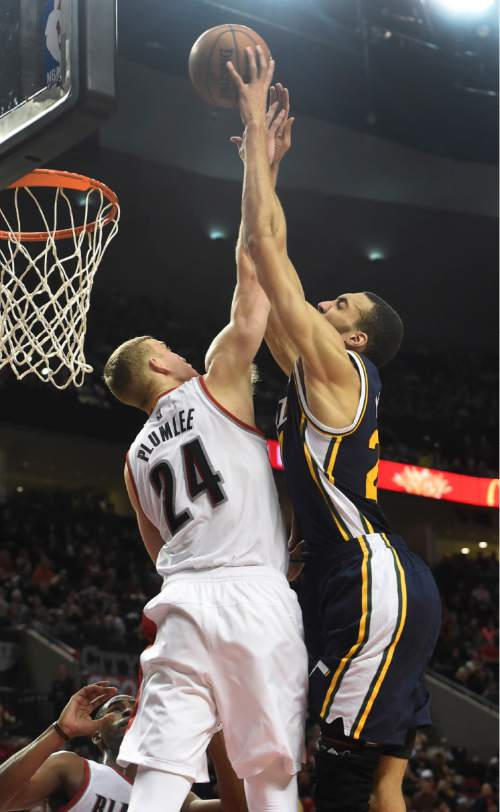 Portland Trail Blazers center Mason Plumlee (24) is called for a foul as he blocks the shot of Utah Jazz center Rudy Gobert (27) during the fourth quarter of an NBA basketball game in Portland, Ore., Sunday, Feb. 21, 2016. The Blazers won 115-111.(AP Photo/Steve Dykes)