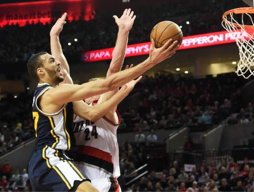 Utah Jazz center Rudy Gobert, left, drives to the basket against Portland Trail Blazers center Mason Plumlee (24) during the first half of an NBA basketball game in Portland, Ore., Sunday, Feb. 21, 2016. (AP Photo/Steve Dykes)