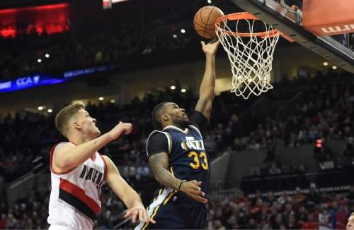 Utah Jazz forward Trevor Booker (33) drives to the basket on Portland Trail Blazers forward Meyers Leonard (11) during the first half of an NBA basketball game in Portland, Ore., Sunday, Feb. 21, 2016. (AP Photo/Steve Dykes)