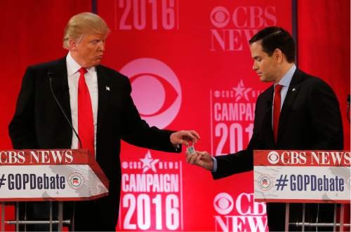 Republican presidential candidate, Sen. Marco Rubio, R-Fla., right, hands Republican presidential candidate, businessman Donald Trump  a tic tac container at a break during the CBS News Republican presidential debate at the Peace Center, Saturday, Feb. 13, 2016, in Greenville, S.C. (AP Photo/John Bazemore)