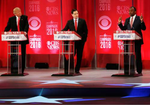 Republican presidential candidate, retired neurosurgeon Ben Carson, right, speaks as Republican presidential candidate, businessman Donald Trump and Republican presidential candidate, Sen. Marco Rubio, R-Fla., look on during the CBS News Republican presidential debate at the Peace Center, Saturday, Feb. 13, 2016, in Greenville, S.C. (AP Photo/John Bazemore)