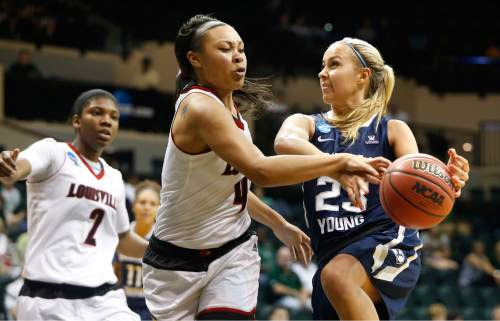 Brigham Young Cougars guard Makenzi Morrison (23) gets pressure from Louisville Cardinals forward Mariya Moore (4) as she goes up for a shot during the first half of an NCAA women's college basketball tournament game, Saturday, March 21, 2015, in Tampa, Fla. (AP Photo/Brian Blanco)