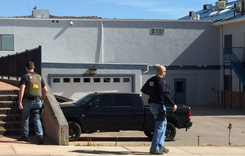 This photo provided by Andrew Chatwin shows law enforcement officers conducting a search at Reliance Electric in Hildale, Utah, Tuesday, Feb. 23, 2016. Police are searching businesses in a polygamous town on the Utah-Arizona border. The U.S. Attorney's Office in Utah said in statement Tuesday that federal, state and local authorities are carrying out actions approved by a court. Officials didn't elaborate, saying court documents are sealed. (Andrew Chatwin via AP)
