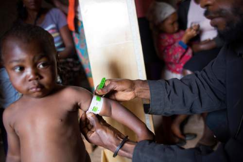 """In this Feb. 15, 2016 photo, community health volunteer Sylvio Fils-Aime examines a child for signs of malnutrition, in Oriani, Haiti. Many Haitians routinely go to bed hungry. But the impact of a yearlong drought is so severe that Haiti is facing """"unprecedented food insecurity,"""" according to the U.N. Office for the Coordination of Humanitarian Affairs. (AP Photo/Dieu Nalio Chery)"""