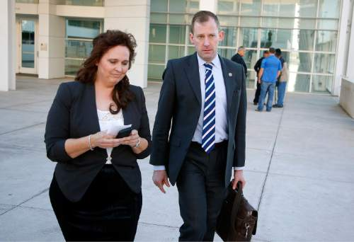 Charlene Jeffs, left, the former sister-in-law of Warren Jeffs, church leader of the Fundamentalist Church of Jesus Christ of Latter Day Saints sect, walks with U.S. Justice Department attorney Sean Keveney, right, as they leave the Sandra Day O'Connor United States District Court together after her day of testimony during a federal civil rights trial against two polygamous towns on the Arizona-Utah line Wednesday, Jan. 27, 2016, in Phoenix. (AP Photo/Ross D. Franklin)