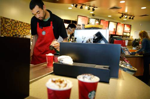 FILE - In this Nov. 24, 2014, file photo, barista Jay Rapp prepares a Chestnut Praline Latte at a Starbucks store in Seattle. Starbucks on Monday, April 6, 2015, said its workers can now have four years of tuition covered for an online college degree from Arizona State University instead of just two, marking the latest sign that companies are rethinking their treatment of low-wage workers. (AP Photo/Ted S. Warren, File)