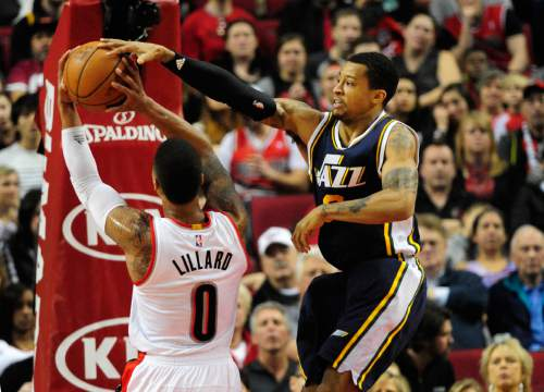 Utah Jazz guard Trey Burke (3) blocks the shot of Portland Trail Blazers guard Damian Lillard (0) during the first half of an NBA basketball game in Portland, Ore., Sunday, Feb. 21, 2016. (AP Photo/Steve Dykes)