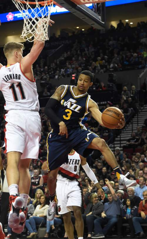 Utah Jazz guard Trey Burke (3) passes the ball as Portland Trail Blazers forward Meyers Leonard (11) defends during the first half of an NBA basketball game in Portland, Ore., Sunday, Feb. 21, 2016. (AP Photo/Steve Dykes)