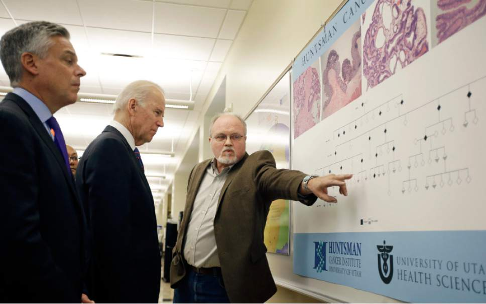 """Patient Gregg Johnson speaks with Vice President Joe Biden during a tour of the research lab at the Huntsman Cancer Institute Friday, Feb. 26, 2016, in Salt Lake City, as part of the White House's cancer """"moonshot,"""" an ambitious effort to double the rate of progress toward curing cancer and ramp up federally funded research on the disease. Johnson's mother died from colon cancer several years ago, but he remains cancer-free due to early screening which gave him knowledge about his genetic status. (AP Photo/Rick Bowmer, Pool)"""