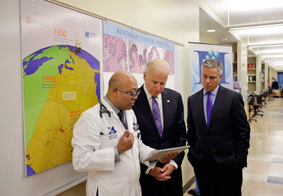 """Dr. Jewel Samadder, left, speaks with Vice President Joe Biden as former Utah Gov. Jon M. Huntsman looks on during a tour of the research lab at the Huntsman Cancer Institute Friday, Feb. 26, 2016, in Salt Lake City, as part of the White House's cancer """"moonshot,"""" an ambitious effort to double the rate of progress toward curing cancer. (AP Photo/Rick Bowmer, Pool)"""