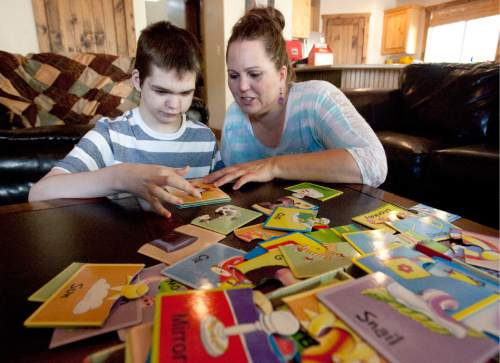Steve Griffin | The Salt Lake Tribune  Jennifer May builds puzzles with her son, Stockton, at their .Pleasant Grove, Utah, home Tuesday Aug. 27, 2013.  Stockton, who has severe seizures, has tried over two dozen  treatments prescribed by doctors. A pharmeceutical version of a cannabis oil has helped reduce seizures for Stockton and other children.