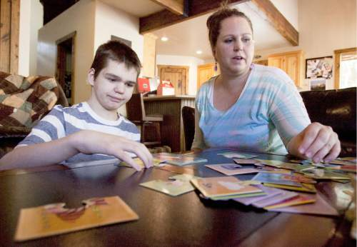 Steve Griffin | The Salt Lake Tribune  Jennifer May builds puzzles with her son, Stockton, at their .Pleasant Grove, Utah, home Tuesday Aug. 27, 2013.  Stockton, who has severe seizures, has tried 25 other treatments prescribed by doctors.