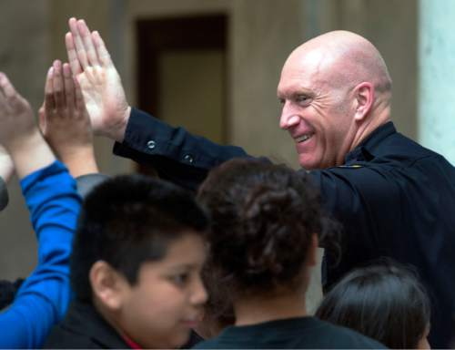 Steve Griffin  |  The Salt Lake Tribune   South Salt Lake City Police Chief Jack Carruth high-fives with a group of children from Pioneer Elementary School in West Valley City, during their visit to the Capitol in Salt Lake City, Monday, February 29, 2016. Carruth took time out from the Utah Chiefs Legislative Luncheon in the Captiol Rotunda to chat with the children as they made their way through the Capiotl. Utah police chiefs attend the annual luncheon to meet with legislators over lunch.