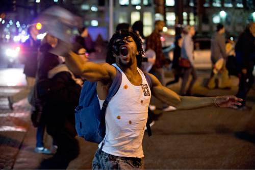 """Lennie Mahler     The Salt Lake Tribune  A man who asked to be identified as """"CJ"""" walks down the street with a crowd of about 500 demonstrating Monday in Salt Lake City against the police shooting of 17-year-old Abdi Mohamed on Saturday."""