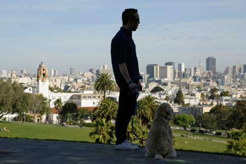 """In this photo taken Wednesday, Feb. 24, 2016, Russell Gipson Shearer is silhouetted with his dog Rocket, who is wearing a Whistle pet tracker GPS-enabled device, at Dolores Park in San Francisco. Technology isn't just for humans. It's also for their furry friends. In Silicon Valley and beyond, a growing number of """"pet-tech"""" startups are selling devices to keep pets safe, healthy, entertained and connected when their owners are away. (AP Photo/Eric Risberg)"""