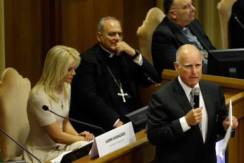 FILE - In this July 21, 2015 file photo, California Gov. Jerry Brown, right, delivers his speech in the Synod Hall as he attends a conference on Modern Slavery and Climate Change at the Vatican. Brown traveled to Italy with real estate developer George Marcus and his wife Judy in their private plane. Brown's office cited an exemption for gifts from friends in not disclosing the flight as part of the $22,000 in gifts and travel in 2015 he reported in his annual disclosure.(AP Photo/Gregorio Borgia,file)