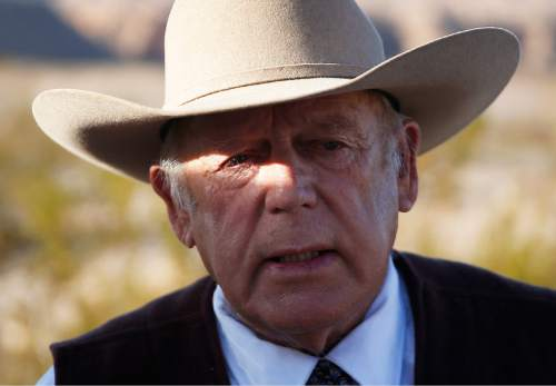 "FILE - In a Wednesday, Jan. 27, 2016 file photo, rancher Cliven Bundy speaks to media while standing along the road near his ranch, in Bunkerville, Nev. A federal grand jury in Nevada indicted Cliven Bundy and four others Wednesday, Feb. 17, 2016, on 16 charges related to an armed standoff near his ranch in 2014 over unpaid grazing fees. Bundy is accused of leading ""a massive armed assault"" of 200 followers to stop federal law agents who were rounding up about 400 of Bundy's cattle on federal lands in April 2014, according to documents filed by U.S. attorneys Wednesday.  (AP Photo/John Locher, File)"