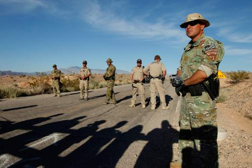 Federal law enforcement officers block a road at the Lake Mead National Recreation Area near Overton, Nev. April 10, 2014. In the foreground are the shadows of people protesting the Bureau of Land Management roundup of cattle owned by Cliven Bundy.  Former BLM director Bob Abbey says Bundy supporters who threatened BLM employees during the roundup should be held accountable. (AP Photo/Las Vegas Review-Journal, John Locher)