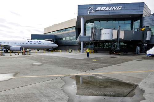 FILE - In this Oct. 19, 2015 file photo, a new Boeing 737-900ER airplane being delivered to United Airlines is parked in front of Boeing's newly expanded 737 delivery center at Boeing Field in Seattle.  Boeing engineers think they have a solution for smelly, grimy airplane bathrooms: ultraviolet light. The aircraft manufacturer has filed a patent for a self-cleaning lavatory that disinfects all surfaces in just three seconds. (AP Photo/Ted S. Warren)